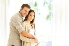 Kobieta w ciąży i mąż patrzeje kamerę zdjęcie royalty free