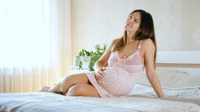 Kobieta w ciąży kłama na łóżku, muska jej round brzucha i marzy, Dziewczyna czekać na dziecka zbiory wideo