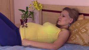 Kobieta w ciąży kłamstwo na łóżku i sztuka z niedźwiedziem bawimy się zbiory wideo