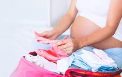 Kobieta w ciąży kocowania walizka, torba dla macierzyńskiego szpitala fotografia royalty free