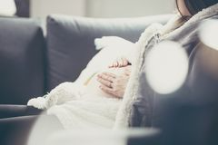 Kobieta w ciąży lying on the beach na kanapie i przytuleniu jej brzuch Fotografia z s zdjęcie stock