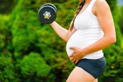Kobieta W Ciąży macania żołądek Podczas gdy Ćwiczący Z Dumbbell fotografia stock