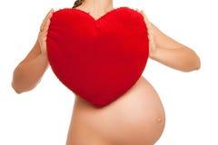 Kobieta w ciąży mienia kierowy symbol nad bielem Fotografia Stock