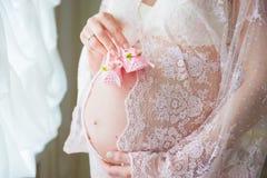 Kobieta w ciąży mienia menchii dziecka buty na jej brzuchu Zdjęcie Royalty Free