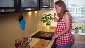 Kobieta w ciąży miesza posiłek w kulinarnej niecce i uśmiech patrzeje kamerę zbiory