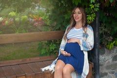 Kobieta w ciąży obsiadanie na ławce, pojęcie szczęśliwa brzemienność zdjęcie stock