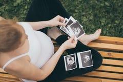 Kobieta w ciąży obsiadanie na loocking ultradźwięku obrazie cyfrowym i ławce Obrazy Royalty Free