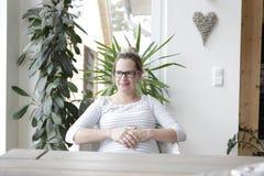 Kobieta w ciąży obsiadanie przy stołem Zdjęcia Royalty Free