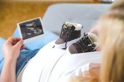 Kobieta w ciąży oczekiwać nowonarodzony i trzymać ultradźwięk fotografię i małych dziecko buty Obrazy Stock