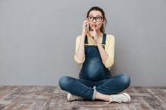 Kobieta w ciąży opowiada telefonem komórkowym i robi cisza gestowi zdjęcie royalty free