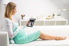 Kobieta w ciąży patrzeje jej dziecka pierwszy sonography wynika na pastylce fotografia royalty free