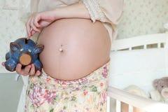Kobieta w ciąży piggi banka moneta zdjęcie stock