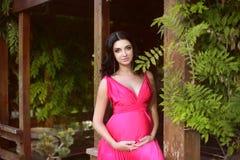 Kobieta w ciąży pozuje w parku Brzemienność, outdoors Szczęśliwy mo Fotografia Royalty Free