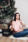 Kobieta w ciąży pozuje z dziecka bodysuit Szczęśliwa kobieta trzyma ślicznego dziecka bodysuit obraz stock