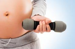 Kobieta w ciąży pracujący z dumbbells out Obrazy Stock