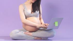 Kobieta w ciąży pracuje na laptopie podczas gdy w Lotosowej pozycji zbiory