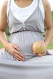 Kobieta w ciąży przedstawienia jabłko w ręce jest jedzącym zdrowiem na dobre t Zdjęcia Royalty Free