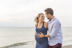Kobieta w ciąży przy plażą z mężem ma zabawę zdjęcie stock