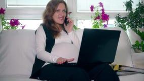 Kobieta w ciąży robi biznesu działaniu z komputerem i wezwaniu w domu zdjęcie wideo