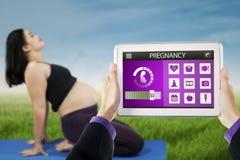Kobieta w ciąży robi joga z brzemiennością app Zdjęcia Royalty Free
