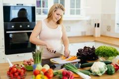 Kobieta w ciąży robi posiłkowi w kuchni fotografia stock