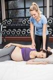 Kobieta w ciąży rozciąganie z jej trenerem zdjęcia royalty free