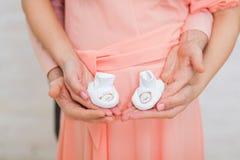 Kobieta w ciąży ` s brzuch z dziecko skarpetami, macierzysta ręka trzyma nowonarodzoną dziecko skarpetę, Obrazy Royalty Free