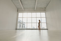 Kobieta w ciąży stojaki okno Obraz Stock