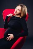 Kobieta w ciąży trzyma jego brzucha przeciw czerni ścianie Obrazy Stock