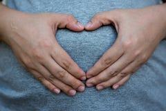 Kobieta W Ciąży trzyma jej ręki w kierowym kształcie na jej dzieci bu Obrazy Royalty Free