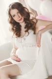 Kobieta w ciąży w białej koszula nocnej w sypialni Obraz Royalty Free