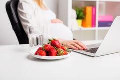 Kobieta w ciąży w biurowy pracującym i mieć truskawki Zdjęcie Stock