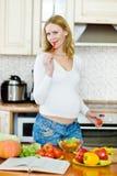 Kobieta w ciąży w kuchni robi sałatki zdjęcia stock