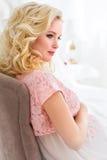 Kobieta w ciąży wewnątrz różowi peignoir siedzi w krześle Zdjęcie Royalty Free