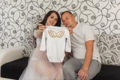 Kobieta w ciąży wraz z jej mężem patrzeje odziewa dla przyszłościowego dziecka fotografia royalty free