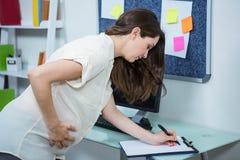 Kobieta w ciąży writing na schowku Obrazy Stock