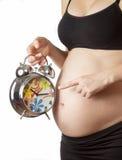 Kobieta w ciąży wskazuje przy budzikiem Zdjęcie Stock