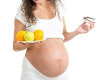 Kobieta w ciąży wybiera między zdrowym jedzeniem i torta iso Zdjęcie Royalty Free