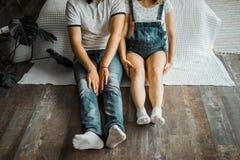 Kobieta w ciąży z brzuchem i jej męża obsiadanie na rękach leżanki i mienia obrazy stock