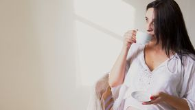 Kobieta w ciąży z filiżanką herbat spojrzenia za okno zdjęcie wideo