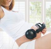 Kobieta w ciąży z hełmofonami na ona żołądek obraz royalty free