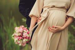 Kobieta w ciąży z jaskrawym bukietem kwiaty i jej mąż ściska brzuszek outdoors Brzemienność, rodzicielstwo, przygotowanie i e, zdjęcie stock