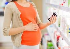Kobieta w ciąży z lekarstwem przy apteką Fotografia Stock