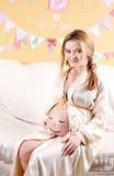 Kobieta w ciąży z malującą twarzą na żołądka tajnym agencie Obraz Stock