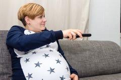 Kobieta W Ciąży z pilot do tv Zdjęcia Royalty Free