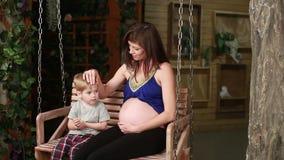 Kobieta w ciąży z starym dzieckiem na huśtawce zdjęcie wideo