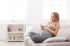 Kobieta w ciąży z szkłem wodny obsiadanie na kanapie Obraz Royalty Free