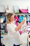 Kobieta w ciąży zakupy odziewa dla jej dziecka Zdjęcie Stock