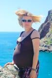 Kobieta w ciąży pozycja na dennym tle zdjęcia stock