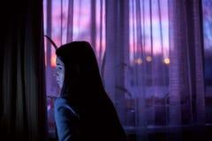 Kobieta w ciemnym pokoju na zmierzchu okno tle Obraz Royalty Free